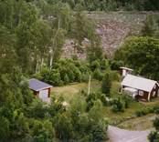 En stuga med uthus och trädgård, intill en ås.
