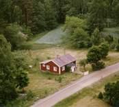 En tillbyggd stuga med trädgård, intill skogen.