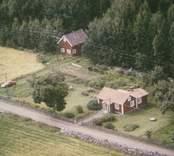 Enkelstuga och ekonomibyggnad vid åkermark i Madesjö.