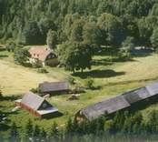 Bostadshus och ekonomibyggnader vid åkermark i Madesjö socken.