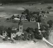 Flygfoto över  Gladhammar. Byn med kyrkan i mitten, hus med vägen genom byn. Kyrkan uppfördes under perioden 1883-1886.