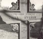 """Gravkors på Fagerhults kyrkogård. Text på korset:""""Gudsords tjenare. Carl Syréen."""""""