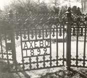 """En grind till en familjegrav. Text på grinden: """"Axebo 1892""""."""