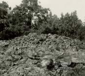 Gravfält på berget 300 meter sydost om Lund, mitt för Gladhammars kyrka. Röse mitt i gravfältet.