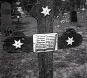 Ett gravkors i trä med stjärnor på Hjorteds kyrkogård.