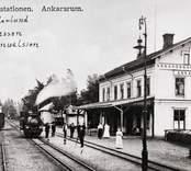 Stationen sedd från spåren med folk utanför. Bredvid ett ensamt lok står tre personer: 1. Stins Cederlund 2. Stionskarl Johnsson 3. Lokförare Samuelsson.