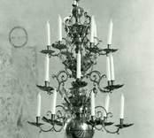 Ljuskrona av mässing för arton ljus i tre kransar.