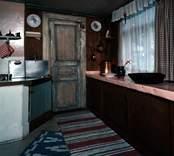 """Interiör från Lindholm-Houges sista bostad på Molinsgatan i Gamla Stan, Kalmar.  Lindholm-Houge, Edvin, 1898-1969, konstnär född i Kalmar och autodidakt. L yrkesarbetade i unga år, men övergick till att helt ägna sig åt konsten. Ivan Hoflund utövade ett betydande inflytande på L under 1930-talet, liksom senare kretsen kring Axel Kargel i Sjöstugan i Borgholm. L utvecklade dock sitt eget sätt att i teckningar, lavyrer och oljemålningar skildra landskap, stadsmiljöer och interiörer. L hade sin styrka i en lyrisk kolorit att jämföra med Carl Kylberg och Karl Isaksson. Ibland talas det om """"Kalmarskolan"""", och där är L ett lysande namn i fotspåren efter Fille Fromén och Ivan Hoflund. 1941 utökar han sitt namn med Houge efter modern för att undvika förväxling med en tavelförsäljare med samma namn i Oskarshamn. L hade en mjukare penselskrift än Kargel och närmar sig stämningen kring Göteborgsmålarna, t.ex. Åke Göransson. Hans samtal blev ofta till monologer. L sägs ha sagt att två skall man vara för ett samtal, tre är redan en för mycket. L tycks ofta arbeta med tre favoritfärger: mörkrött, smaragdgrönt och violett. L:s första separatutställning dröjde till 1957 och ägde rum i Stockholm. Den fick strålande recensioner och L beskrevs som en """"intim expressionist"""". L var även en skicklig skribent som publicerade artiklar i dagspressen och några mindre skrifter. Han var till sin natur skygg och tillbakadrage, närmast en enstöring och bodde i enkla bostäder, bl.a. i ett rivningshus på Tullslätten och sist på Molinsgatan."""