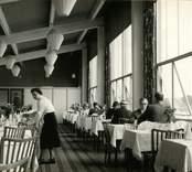 """Interiör av den nya Restaurang Slottsholmen Restaurang Slottsholmen: Den 15 juni 1950 brann den """"gamla"""" restaurangen ned. Den 18 november påbörjades uppförandet av den nya restaurangen, som invigdes den 17 juli 1952. För publicering av bilden hänvisas till ägaren via Kalmar läns museum"""