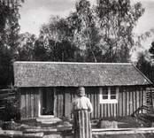 """Emma Åström """"Tupp-Emma"""" utanför sin stuga."""