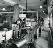 A22767a KLM 33250 Tappning. Rörmontör Petersson är med på bilden fast han inte hör till bryggeriet. Foto taget 1955 Under åren 1946-1950 byggdes Kalmar bryggerier om och ut på grund av koncentrationen av öltillverkning till Kalmar. Bryggerierna i Mörbylånga, Grönskogsbryggeri i Nybro samt i Mönsterås slogs ihop.