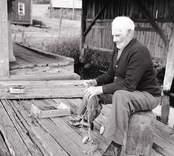 Karl Pettersson lagar nät utanför sjöboden. Foto: 26/07 1955.