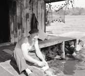 Fiskare rensar fisk utanför sjöbod.