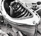 Einar Nilsson bottenmålar sin fiskebåt på havsudden.