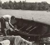 En man underhåller sin båt på Marsö.