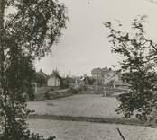 """""""Torsås"""", [två järnvägsspår in mot samhället, Torsås socken]. Fotografi på brun kartong; 9 x 14 resp 14 x 19 cm. Fotograf troligen C G Rosenberg 1917."""