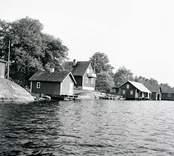 Vy med sjöbodar och bostadshus på Älö i Misterhult. Foto: 28/07 1955.