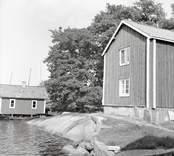Hus och sjöbod i bakgrunden på Älö.