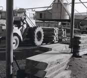 En traktor, omgiven av virkeshögar, på Elfverson & Co i Påryd.