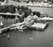 """Flygfoto över den gamla restaurangen och kallbadhuset. Restaurang Slottsholmen: Den 15 juni 1950 brann den """"gamla"""" restaurangen ned. Den 18 november påbörjades uppförandet av den nya restaurangen, som invigdes den 17 juli 1952. För publicering av bilden hänvisas till ägaren via Kalmar läns museum"""