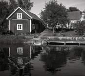 En bod och bostadshus med vatten och brygga i Figeholm.