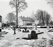 Absiden på Madesjö kyrka och prästgården i fonden.
