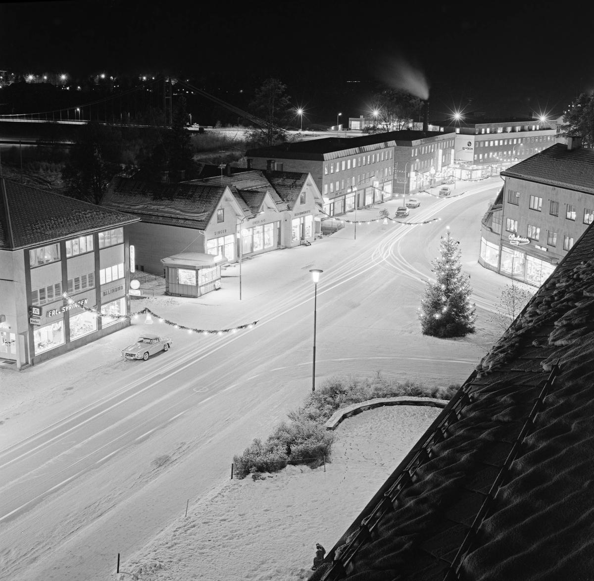 Vinterbilde fra Storgata i Elverum i Hedmark, antakelig tatt en kveld like før jul i 1968.  Fotografiet er tatt fra tårnet i rådhuset, nordover tettstedets hovedgate, som på dette tidspunktet lå «badet» i lys fra gatelykter og bygninger, med noen få parkerte biler langs fortauskantene, men ellers helt uten trafikk.  Det sto ei julegran i krysset mellom Storgata og St. Olavs gate, og Storgata var prydet med ranker av gran, ispedd lyspunkter, som hang på tvers av gateløpet.  Med unntak av Smedstua eller Bekk, det trefløyete trehuset som sto vis a vis St. Olavs gates møte med Storgata, var bebyggelsen langs gateløpet preget av funkispreget bebyggelse, reist åra etter 2. verdenskrig, som en konsekvens av at kommunesenteret i Elverum ble bomberammet i forbindelse med den tyske okkupasjonen i 1940. (Foto/Photo)