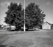 Hamnplanen i Figeholm, ekonomibyggnad, parksoffa och vedtrave.