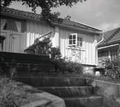 Vy från Figeholm, bostadshus med träpanel och sadeltak och trappa.