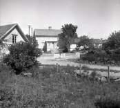 Vy från Figeholm, bostadshus med träpanel och sadeltak.