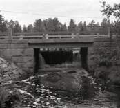 Bro över Hagbyån nordost om Strömsholm i Nybro kommun. Foto, nedströms V-bron från söder.