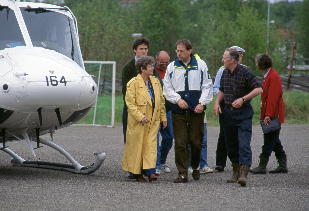 Daværende statsminister Gro Harlem Brundtland (f. 1939), flankert av daværende Elverum-ordfører Per-Gunnar Sveen (f. 1965) og daværende direktør ved Norsk Skogbruksmuseum, Yngve Astrup (f. 1943), fotografert ved helikopteret som transporterte Brundland og to av hennes statsråder til Elverum i juni 1995, under den til da største flommen i Sør-Norge siden 1789. Flommen kulminerte den om kvelden 2. juni, og statsministeren og statsrådene hennes besøkte flomområdene bare noen timer før dette skjedde. Bak Brundtland ser vi daværende energi- og næringsminister Jens Stoltenberg (f. 1959). Stoltenberg ble seinere statsminister (2000-2001 og 2005-2013) og generalsekretær i NATO (fra 2014).  Den andre statsråden som var med på denne befaringa, justisminister Grethe Faremo (f. 1955) befant seg bak ordfører Sveen da dette fotografiet ble tatt. Mannen mellom Brundtland og Stoltenberg og Sveen er også en Arbeiderparti-veteran, Kjell Borgen (1939-1996), som på dette tidspunktet var fylkesmann i Hedmark. Den uniformerte mannen bak Astrup er sannsynligvis daværende politiinspektør Jorstein Løken (f. 1962) (Foto/Photo)