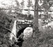 Bro över bäck i Fårbo samhälle väg Ficksjövägen i Oskarshamns kommun. Foto, uppströms från väster.