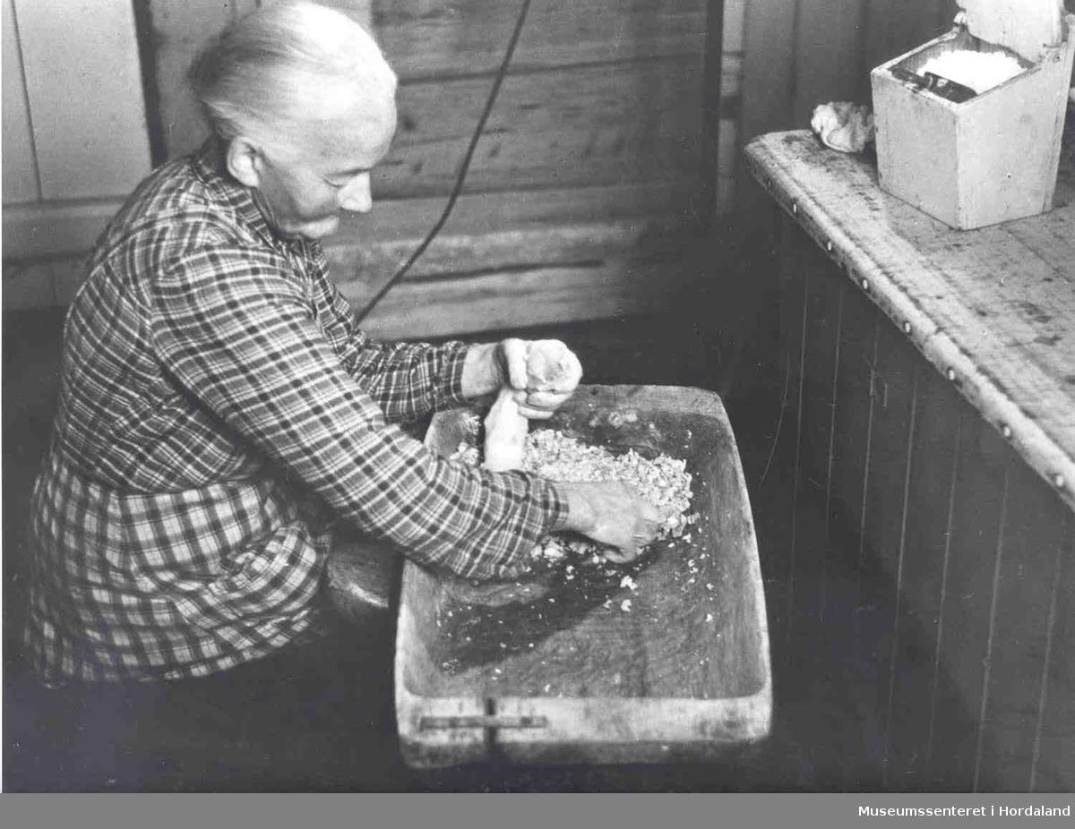 Havrå. Kone som set og stappar pølse for hand. Kjøkken med tømmerveggar. Mjølboks. Trau.  (Foto/Photo)