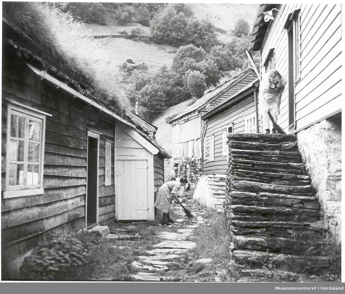 Havrå.Kvinner som soper utforbi husa i eit klyngjetun. Tre våningshus, ein flor/løe. Eine våningshuset er med torvtak. Steintrapp. Bratte lier med lautre i bakgrunnen (Foto/Photo)